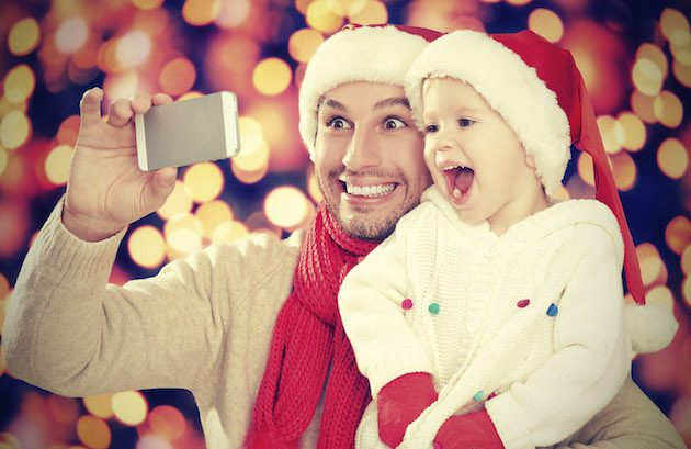 Christmas Day Lunch at the North Pole: selfe in Christmas. happy family dad playing with daughter and photographed on mobile phone